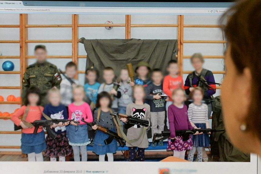 A woman looks at a computer screen displaying a photo that shows boys and girls posing with weapons at a kindergarten in Saint Petersburg, Moscow on Feb 26, 2015. -- PHOTO: AFP