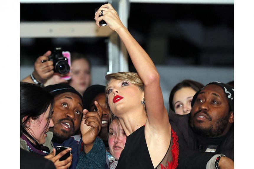 Singer Taylor Swift poses for selfies with fans as she arrives for the BRIT music awards at the O2 Arena in Greenwich, London, on Feb 25, 2015. -- PHOTO: REUTERS
