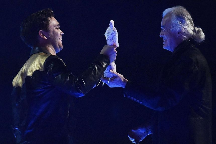 Mike Kerr (left) of Royal Blood celebrates winning the British Group award presented to him by Jimmy Page at the BRIT music awards at the O2 Arena in Greenwich, London, on Feb 25, 2015. -- PHOTO: REUTERS