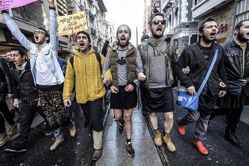 Turkish men wearing skirts demonstrate in Istanbul, to support women's rights in memory of 20-year-old Ozgecan Aslan, who was murdered after she resisted an alleged attempted rape in the southern city of Mersin, on Feb 21, 2015. -- PHOTO: AFP
