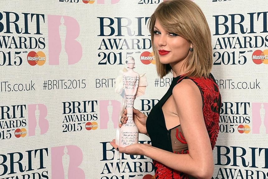 US singer Taylor Swift poses with her International Female Solo Artist award at the Brit Awards 2015 in London on Feb 25, 2015. -- PHOTO: AFP