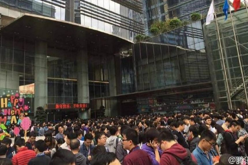 Tencent employees queuing outside the company's headquarters in Shenzhen as they await their turn to receive a red packet from founder Pony Ma Huateng. -- PHOTO: WEIBO