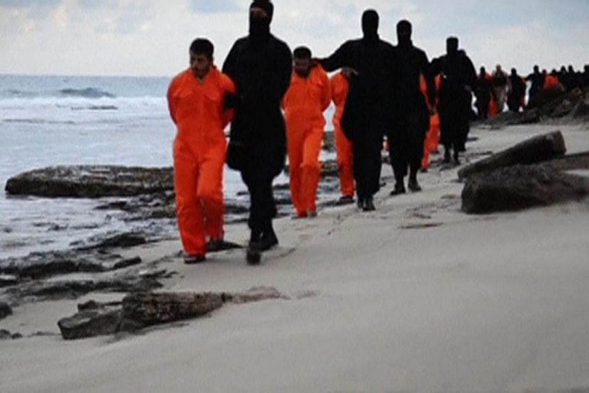 Egyptian Christians held captive by ISIS being marched along a beach - thought to be near Tripoli, Libya - before they were beheaded. This still image from an undated video was made available on social media on Feb 15.