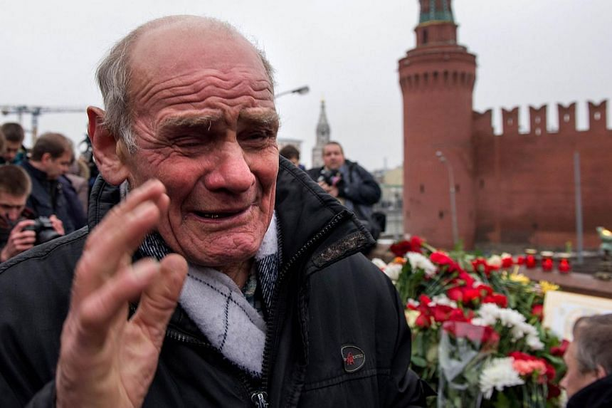 A man cries at the spot, where Russian opposition leader Boris Nemtsov was shot dead, near Saint-Basil's Cathedral, in the centre of Moscow on Feb 28, 2015. Russian President Vladimir Putin promised the mother of Nemtsov on Saturday that everything w