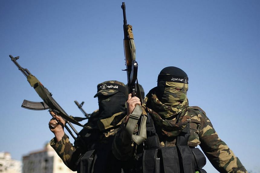 Palestinian militants leave after representatives of various Palestinian armed factions held a news conference to condemn the decision of an Egyptian court that banned Hamas' armed wing, in Gaza City, Feb 5, 2015. -- PHOTO: REUTERS