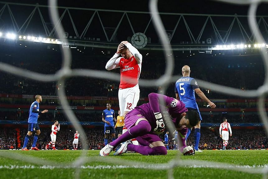 Arsenal striker Olivier Giroud (in red) reacts after missing a chance to score during his match against AS Monaco at the UEFA Champions League in London on Feb 25, 2015. Giroud has vowed to bounce back from his Champions League hu