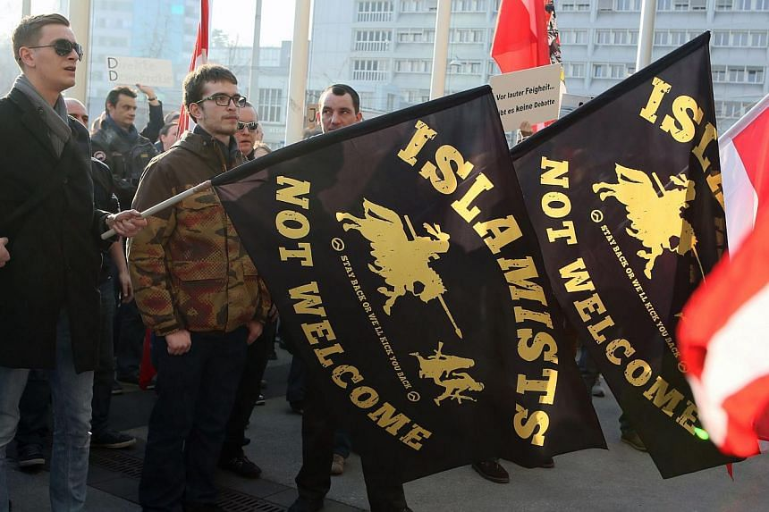 "Participants hold flags during a rally of Anti-Islam movement Pegida in Linz, Austria on Feb 21, 2015. The German-based Pegida movement, which opposes what it calls the ""Islamisation"" of Europe, was staging its first demonstration on British soi"