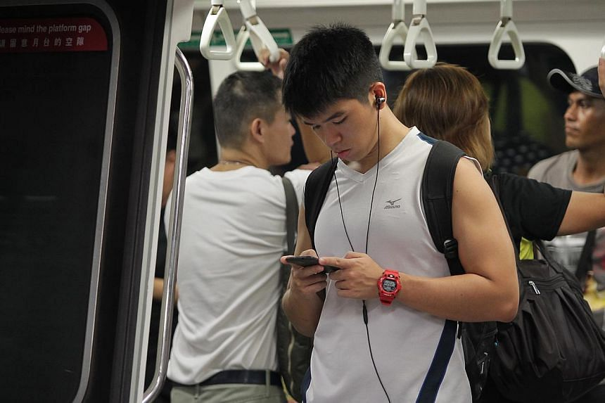 A commuter listening to music using earphones in a Singapore train on March 27 2014.More than one billion young people risk damaging their hearing through listening to loud music, the World Health Organisation said on Friday. -- ST FILE PHOTO