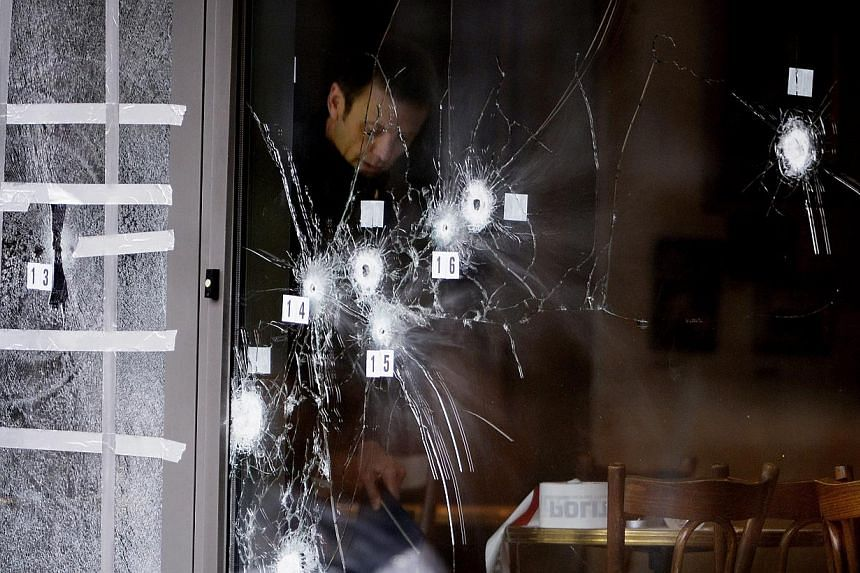 Police forensics inspect bullet holes in the door of Krudttoenden cafe where the terrorist attack started in Copenhagen, Denmark, Feb 15, 2015. A third alleged accomplice was charged on Saturday. -- PHOTO: EPA