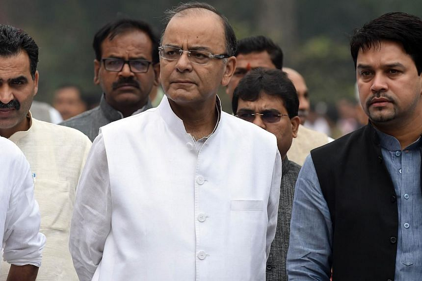 Indian Finance Minister Arun Jaitley walks with party officials and Members of Parliament after a Bharatiya Janata Party (BJP) Parliamentary Board meeting at Parliament House in New Delhi on Feb 24, 2015. -- PHOTO: AFP