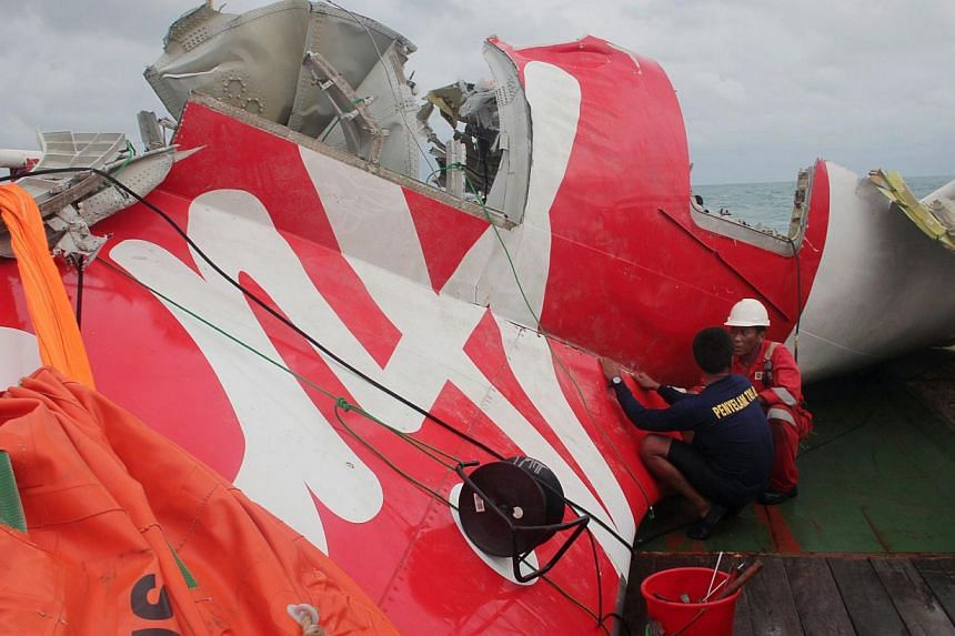 In this file photograph taken on Jan 10, 2015, an Indonesian diver and an official examine the wreckage from AirAsia flight QZ8501 after it was lifted into the Crest Onyx ship at sea.Indonesia has retrieved the final major part of the fuselage