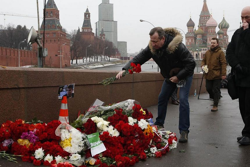 People come to lay flowers at the site, where Boris Nemtsov was shot dead, with St. Basil's Cathedral (right) and the Kremlin walls seen in the background, in central Moscow, on Feb 28, 2015. -- PHOTO: REUTERS