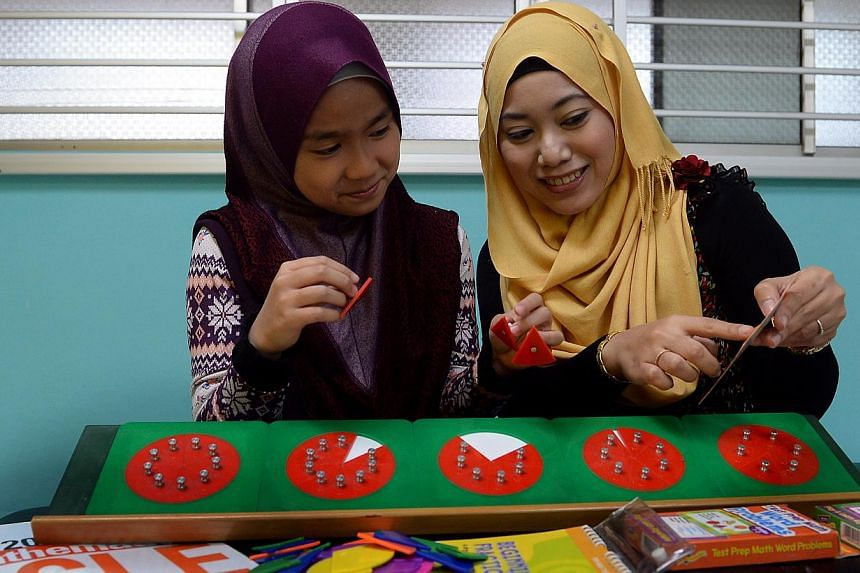Ms Nurhidayah Mohamad Ismail (right), principal of Genius Young Minds, showing Naily Afiqah Zailanio, a student from Irsyad Zuhri Madrasah, how to use the 'fraction board' so that she can see and understand the concept of fractions better. -- BH PHOT