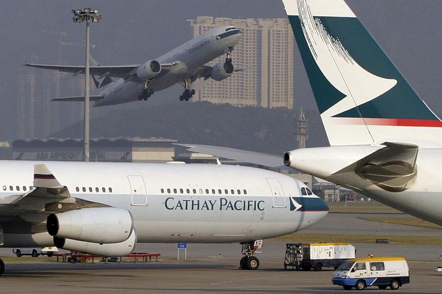 Cathay Pacific jets sit on the runway at Hong Kong's Chek Lap Kok airport on Friday, October 17, 2003 as another takes off in the background. -- FILE PHOTO: BLOOMBERG