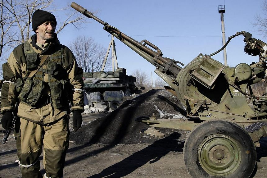 A pro-Russian rebel walks past a twin-barrelled anti-aircraft gun in the streets of Debaltseve, in the Donetsk area of Ukraine on Feb 21, 2015. Spain on Friday arrested eight citizens who recently returned from fighting alongside pro-Russian rebels i