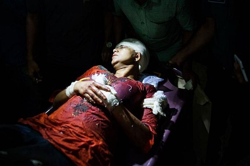 Avijit Roy's wife Rafida Ahmed Banna is carried on a stretcher after she was seriously injured by unidentified assailants, in Dhaka on Feb 27, 2015. Her husband was killed in the attack. -- PHOTO: AFP