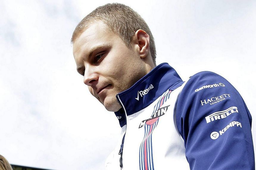 Finnish Formula One driver Valtteri Bottas of Willliams walks in the paddock during pre-season testings at Montmelo racetrack in Barcelona, northern Spain, Feb 26, 2015. -- PHOTO: EPA