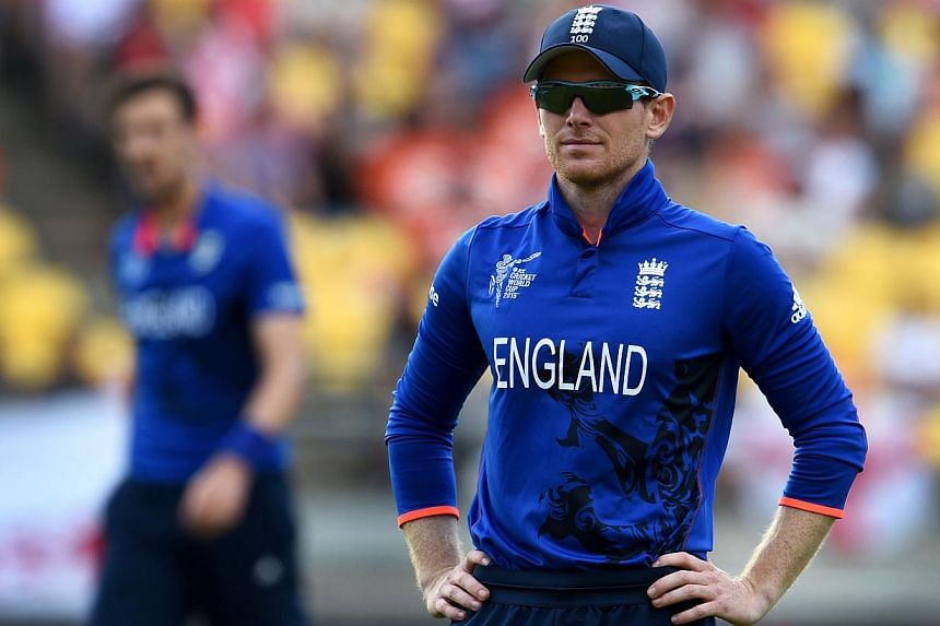 England captain Eoin Morgan watches the ball return from the boundary after Steve Finn (left) was hit for four by the Sri Lanka batsman during their 2015 Cricket World Cup Group A match in Wellington on Mar 1, 2015. -- PHOTO: AFP