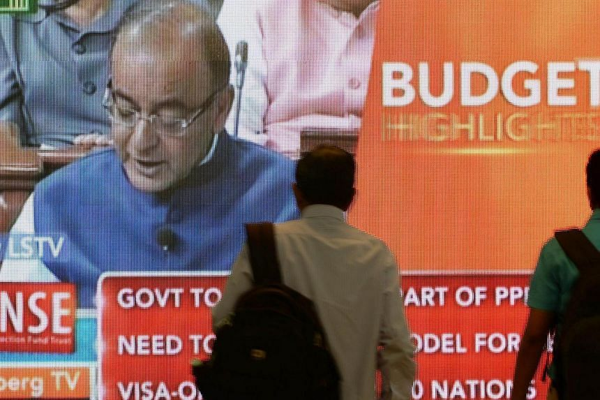 Indian office workers walk past a digital screen showing Indian Finance Minister Arun Jaitley delivering his Budget speech at Parliament in New Delhi, on Feb 28, 2015.The Indian government's budget was praised on Sunday, Mar 1, as balancing the