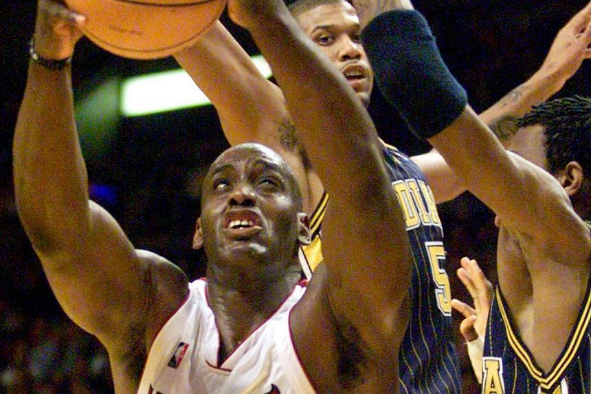 Miami Heat forward Anthony Mason (left) attempts to shoot around the defensive pressure of Indiana Pacers guard Jalen Rose (centre) and forward Jonathan Bender (right) during the second quarter of NBA play in Miami, Florida in this file photo from Fe
