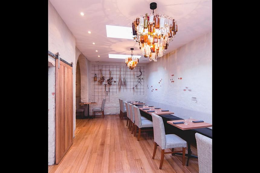 At Ethos Eat Drink, salvaged timber has been reused and old apothecary bottles transformed into chandeliers (above).--PHOTO: ETHOS EAT DRINK