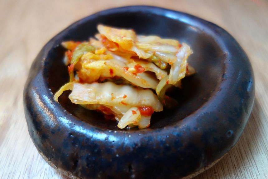 At Ethos Eat Drink, salvaged timber has been reused and old apothecary bottles transformed into chandeliers. The menu includes a broth with tomato, barley and leek and snacks that include crunchy kimchi (above).--PHOTO: TAN HSUEH YUN