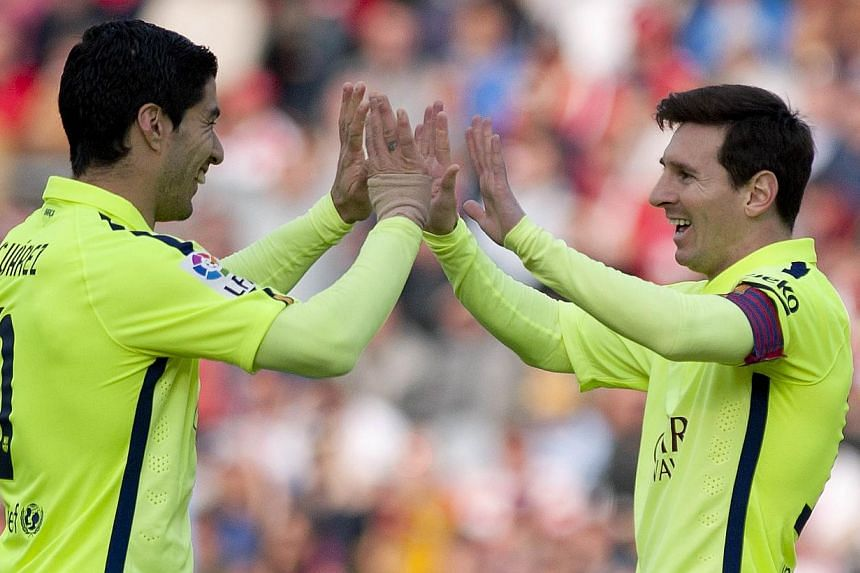 Barcelona's Argentinian forward Lionel Messi (right) celebrates a goal with teammate Luis Alberto Suarez during their match against Granada on Feb 28, 2015. -- PHOTO: AFP