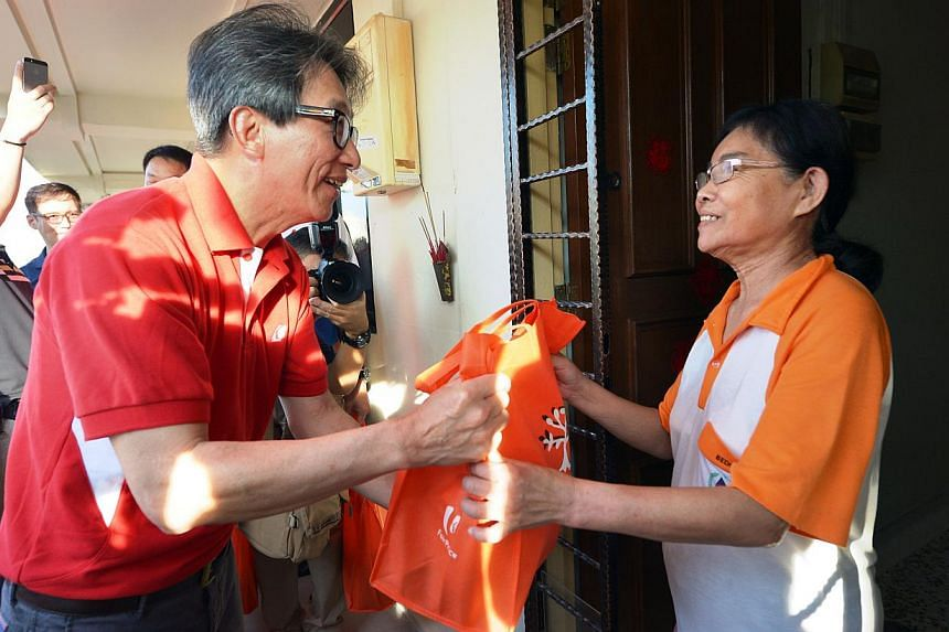 Minister in the Prime Minister's Office and grassroots adviser for East Coast GRC, Mr Lim Swee Say (left). He joined the volunteers in distributing the items. -- ST PHOTO: ALPHONSUS CHERN