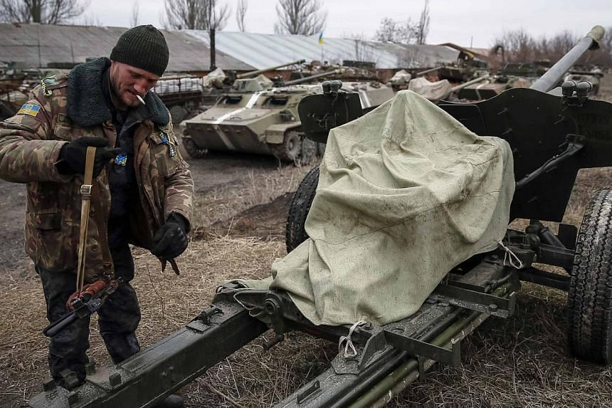A Ukrainian serviceman stands near armoured personnel carriers, military vehicles and cannons at their new position as they pull back from the Horlivka region, near Druzhkivka, eastern Ukraine, Feb 28, 2015. -- PHOTO: REUTERS