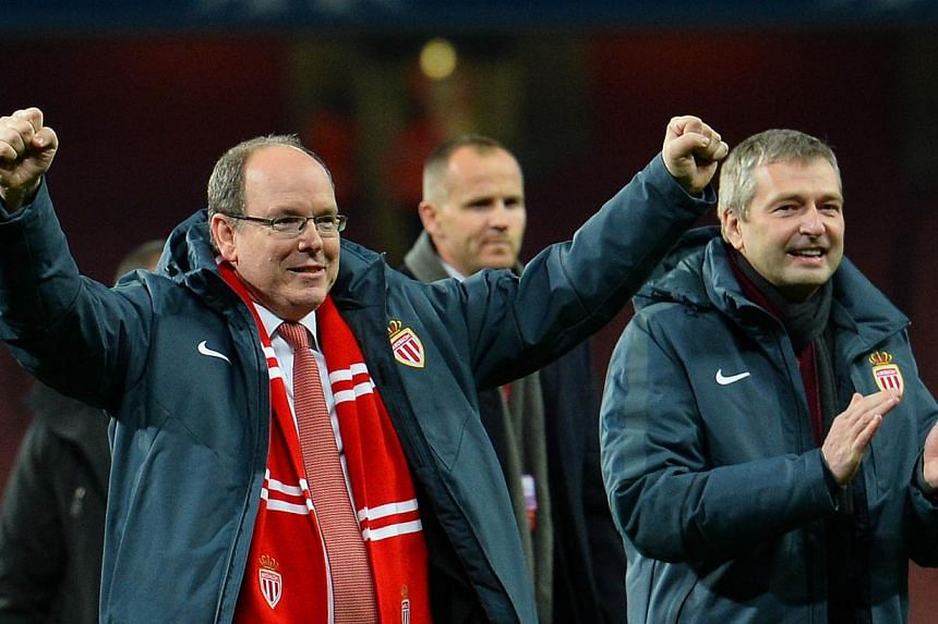 Prince Albert II of Monaco (left) celebrates on the field with Monaco's Russian president Dmitry Rybolovlev (right) after the final whistle of the UEFA Champions League round of 16 first leg football match between Arsenal and Monaco at the Emirates S