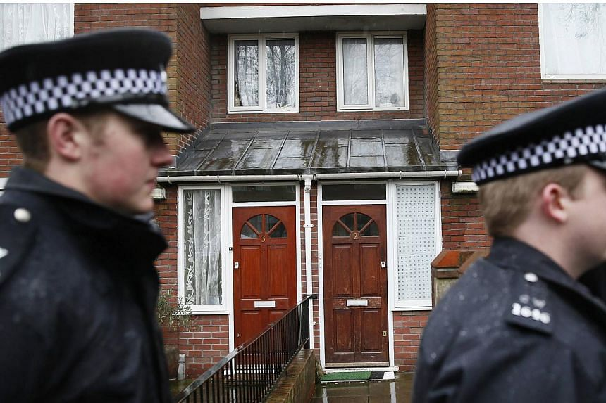 """Two police officers walk outside a flat in London on 26 Feb, 2015.Kuwaiti authorities are closely monitoring several relatives of """"Jihadi John"""" who live and work in the Gulf emirate where the Islamic State in Iraq and Syria (ISIS) executioner w"""