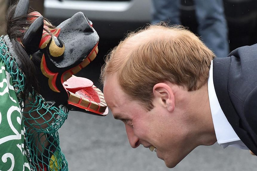 Britain's Prince William (right) being greeted by a lion dancer during his visit to the Chime of Hope Shopping Centre in Onagawa, Miyagi prefecture, Japan, on March 1, 2015. -- PHOTO: EPA