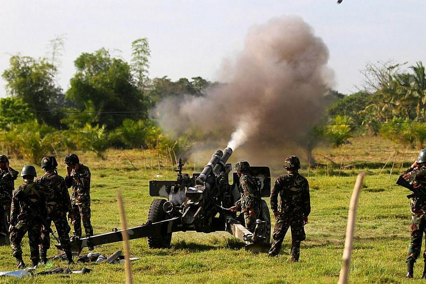"""In this photo taken on Feb 28, 2015, government forces of the 6th Infantry Division fire a105 Howitzer canon in Maguindanao, Southern Philippines.The Philippine military is trying to capture a bombmaker it believes is being """"coddled"""" by Filipin"""