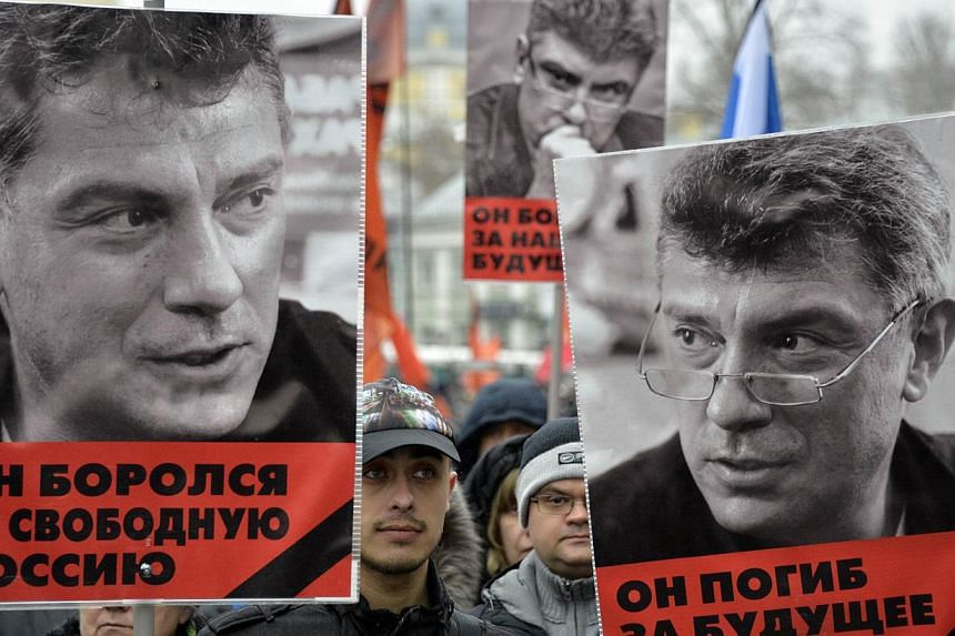 """Russia's opposition supporters carrying portraits of Kremlin critic Boris Nemtsov during a march in central Moscow on March 1, 2015. Words under the portraits read """"He fought for a free Russia"""" and """"He died for the future of Russia"""". -- PHOTO: AFP&nb"""