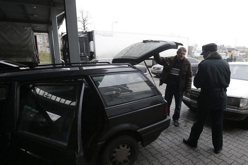 A Lithuanian border guard inspects a car as it enters Lithuania at a border crossing with Russia in Kybartai on Dec 16, 2014.Singapore must keep up its strong defence and can learn from Lithuania, said Defence Minister Ng Eng Hen on Sunday. --