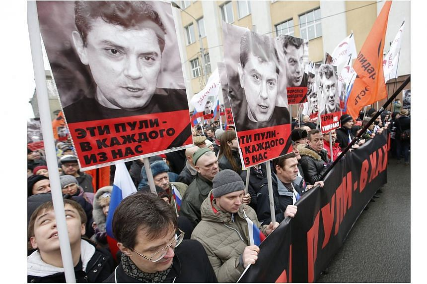 People holding posters of Kremlin critic Boris Nemtsov, who was shot dead on Friday night, during a march to commemorate him in central Moscow on March 1, 2015. -- PHOTO: REUTERS
