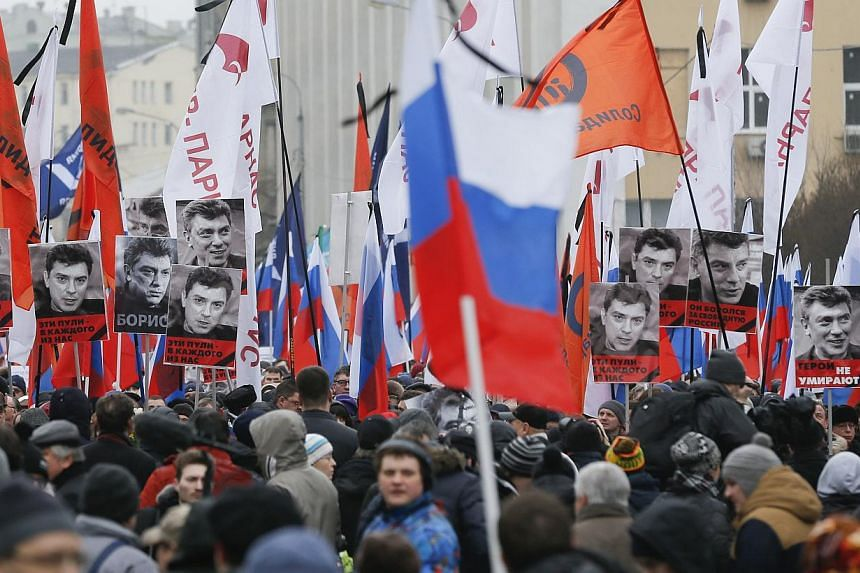 People holding flags and posters during a march to commemorate Kremlin critic Boris Nemtsov, who was shot dead on Friday night, in central Moscow on March 1, 2015. -- PHOTO: REUTERS