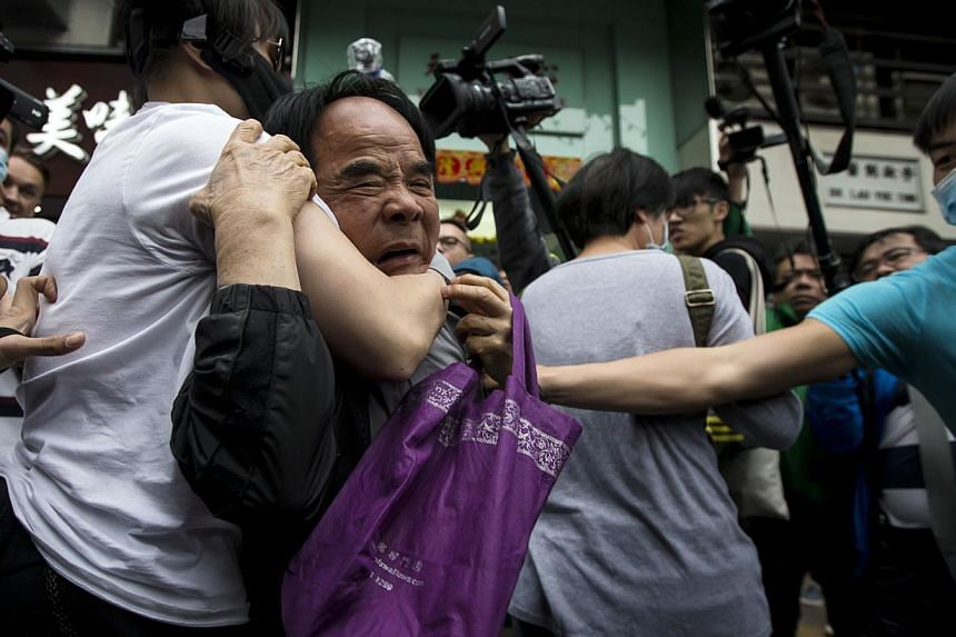 Protesters restraining a man (centre) who allegedly beat other fellow protesters during a demonstration against mainland traders, at Yuen Long in Hong Kong on March 1, 2015. At least three people were arrested after about 400 protesters clashed with