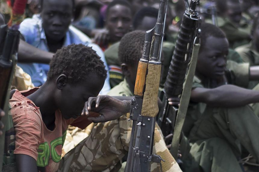 Child soldiers sitting on with their rifles at a ceremony of the child soldiers disarmament, demobilisation and reintegration in Pibor, South Sudan overseen by UNICEF and partners on Feb 10, 2015. The UN children's agency said on Sunday, March 1