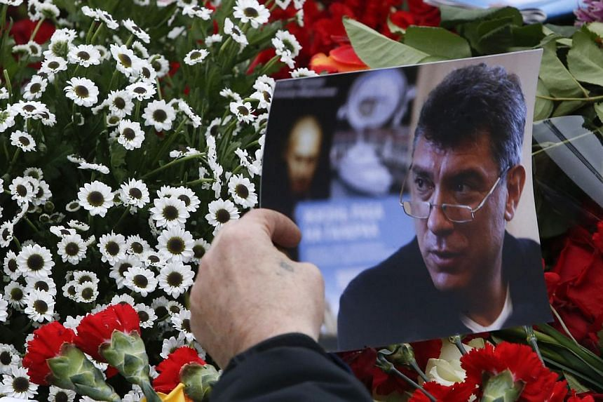 A visitor holds a photo at the site where Boris Nemtsov was recently murdered, in central Moscow, Feb 28, 2015. Nemtsov had enemies politically and personally. Even among the opposition, his outsized character pulled some into his orbit and push