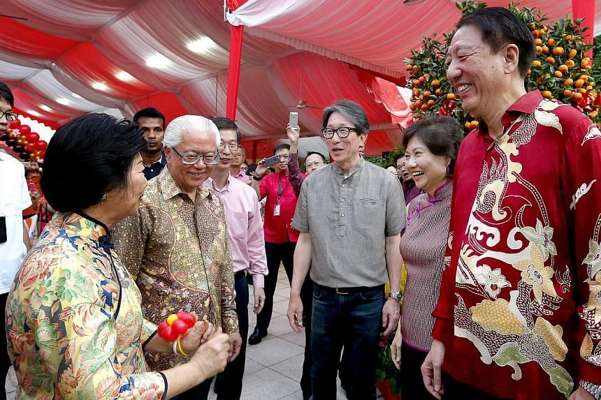 President Tony Tan Keng Yam talking to Minister in the Prime Minister's Office Lim Swee Say (third from right) and Deputy Prime Minister Teo Chee Hean (right) at the annual Chinese New Year Garden Party held on the Istana Lawn on March 1, 2015.
