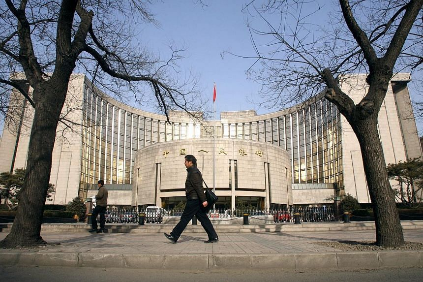 People walking past the People's Bank of China in Beijing, China, on Jan 8, 2008. China's central bank cut benchmark interest rates for the second time in three months as disinflation gives room to step up support for the nation's slowing economy. --
