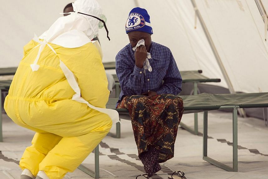 A health worker wearing protective gear attends to a newly admitted suspected Ebola patient in a quarantine zone at a Red Cross facility in the town of Koidu, in Eastern Sierra Leone in this Dec 19, 2014 file photo. -- PHOTO: REUTERS
