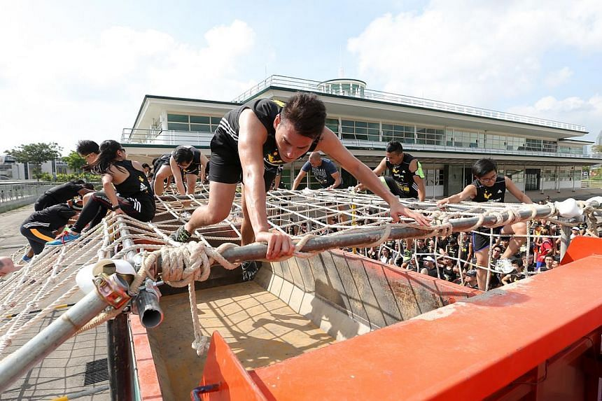 Participants clambering over an obstacle consisting of a vertical wall of rope webbing tied across the top of a truck. More than 3,700 participants pounded through the heart of the Central Business District on Sunday to tackle the Men's Health Urbana