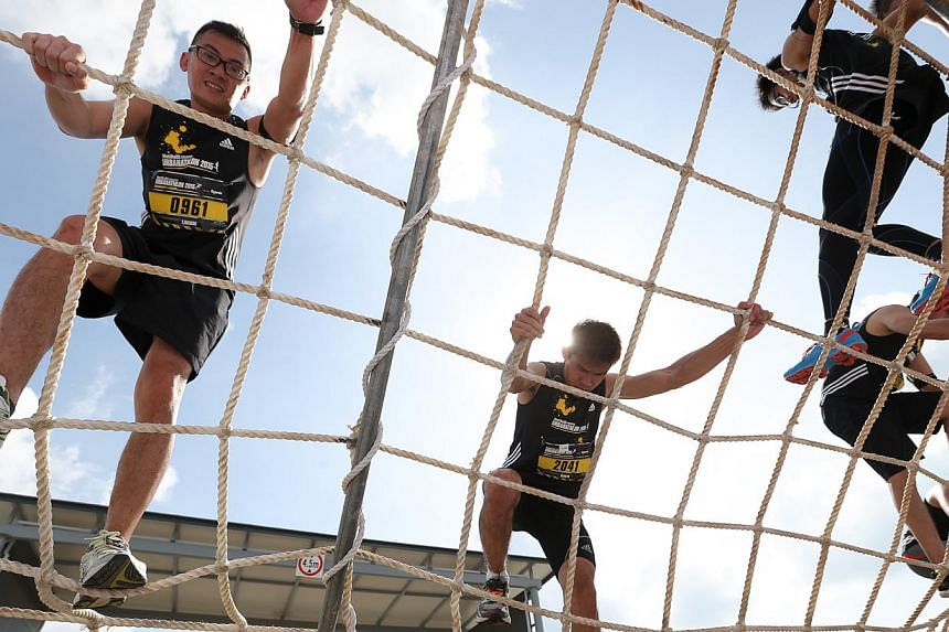 Participants at an obstacle where they get on all fours to climb up a vertical wall of rope webbing to the top of a truck, turn around and descend the sloping rope web on the other side feet first. -- ST PHOTO: ONG WEE JIN