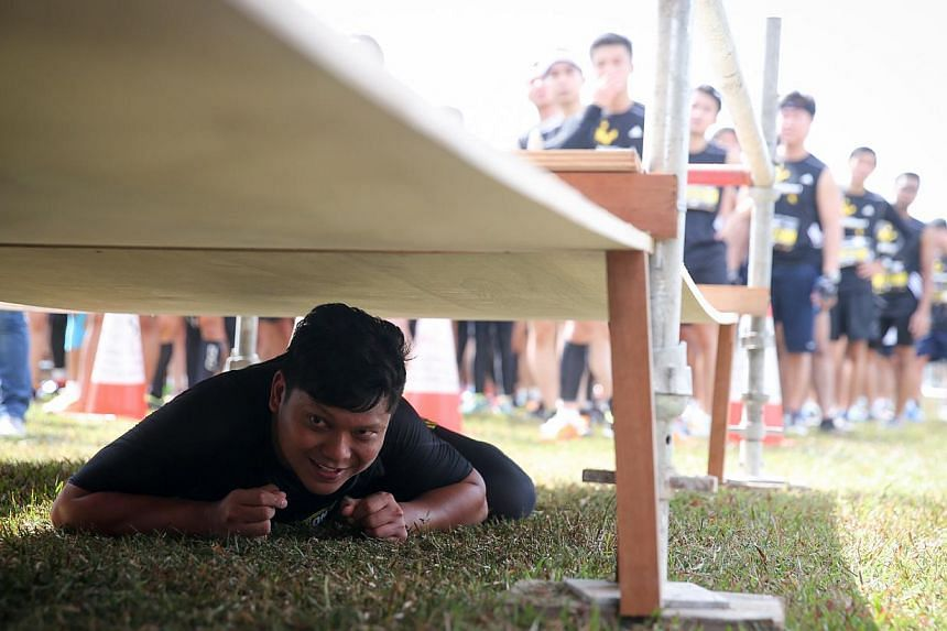 A participant clears the mystery obstacle by first doing a leopard crawl, followed by a climb up a tower and finished by leaping down unto a safety mattress. -- ST PHOTO: ONG WEE JIN