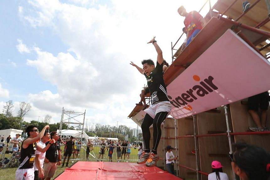 Participants finishing off the race by jumping off a tower, which was part of the mystery obstacle during the event. -- ST PHOTO: ONG WEE JIN