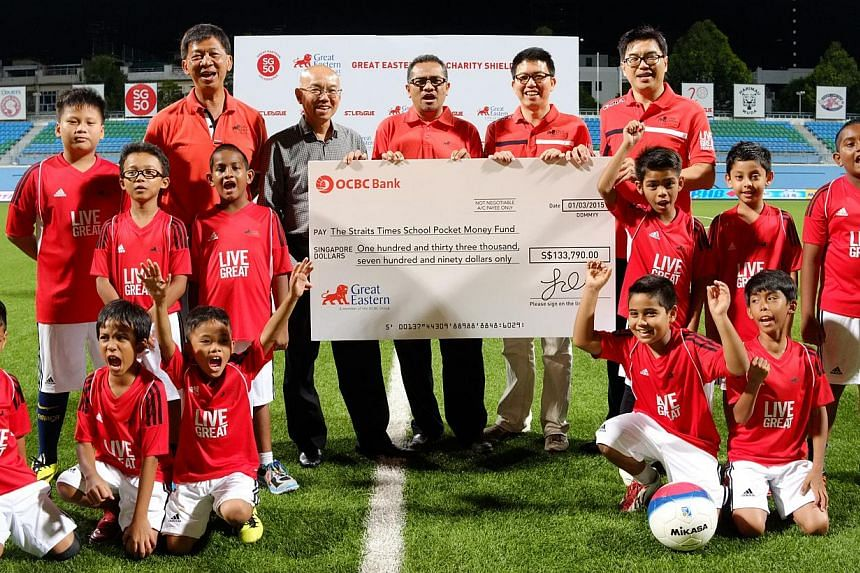 Great Eastern's Singapore CEO, Dr Khoo Kah Siang (extreme right, holding checque) presents the cheque for $133,790 to Mr Han Fook Kwang (in grey), Chairman of The Straits Times School Pocket Money Fund at the Great Eastern SG50 Charity Shield at the