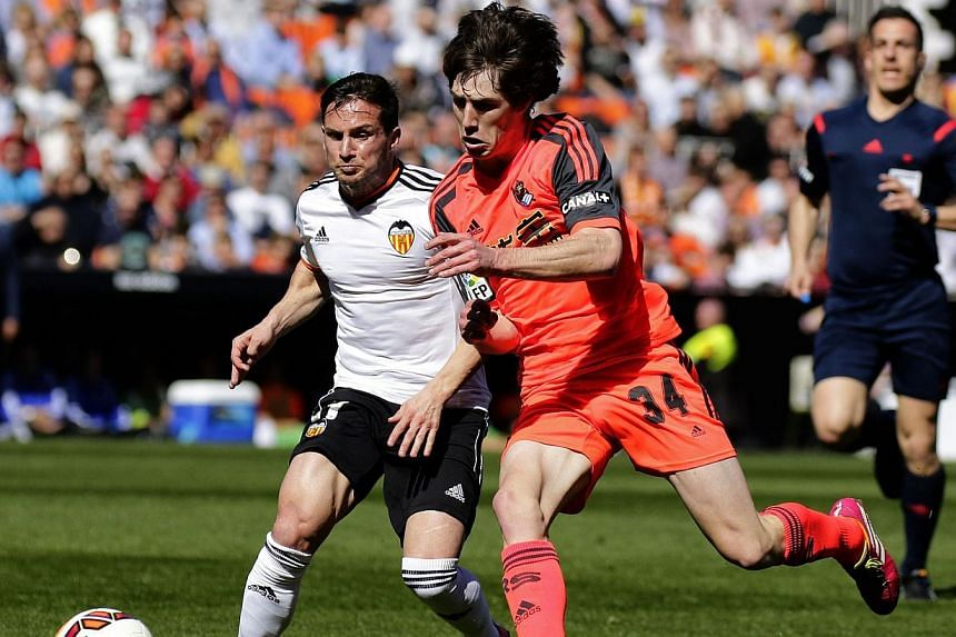 Valencia's Argentinian forward Pablo Piatti (left) vies with Real Sociedad's defender Julen Etxabeguren during the Spanish league football match Valencia CF vs Real Sociedad de Futbol at the Mestalla stadium in Valencia on March 1, 2015. -- PHOTO: AF