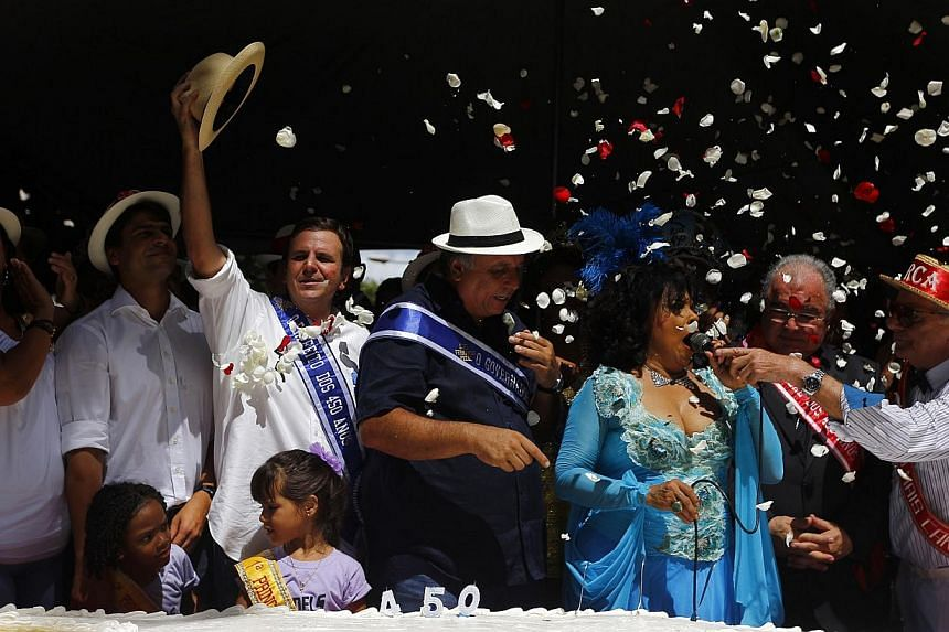Mayor Eduardo Paes holding up his hat as he and Rio de Janeiro residents tuck into a monster birthday confection to mark the Brazilian city's 450th anniversary. -- PHOTO: REUTERS